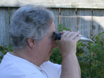 Newfield uses a refractometer to measure flower nectar.